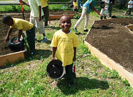 Children volunteers helping plant a pollinator garden